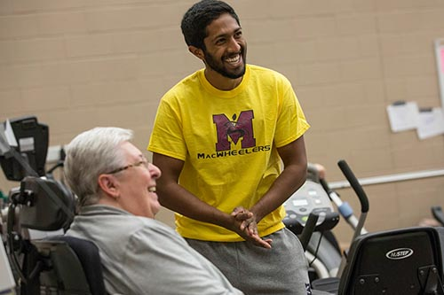 Image of researcher from Kinesiology helping an elderly member of the community do exercises as part of a health study in a gym