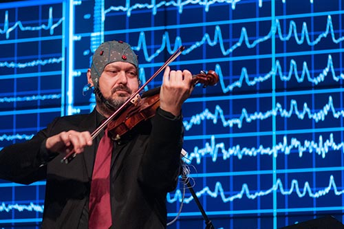 Image of violinist playing music with an EEG cap on his head measuring brain activity in the McMaster LIVE Lab
