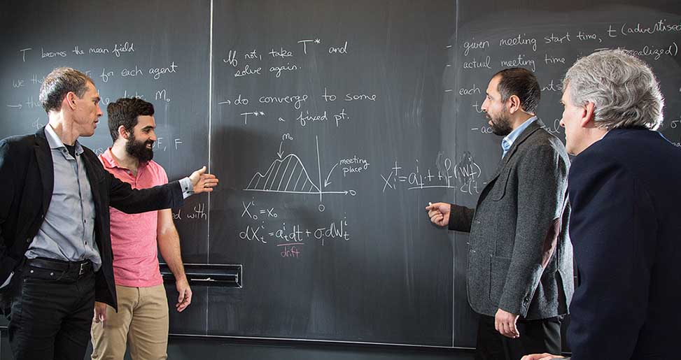 Students discussing calculations with black board