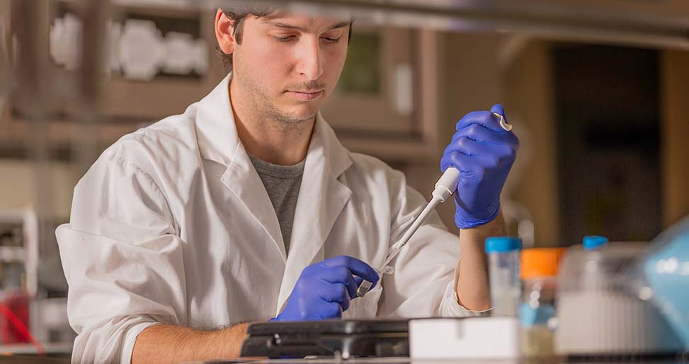 student in a lab using pipette