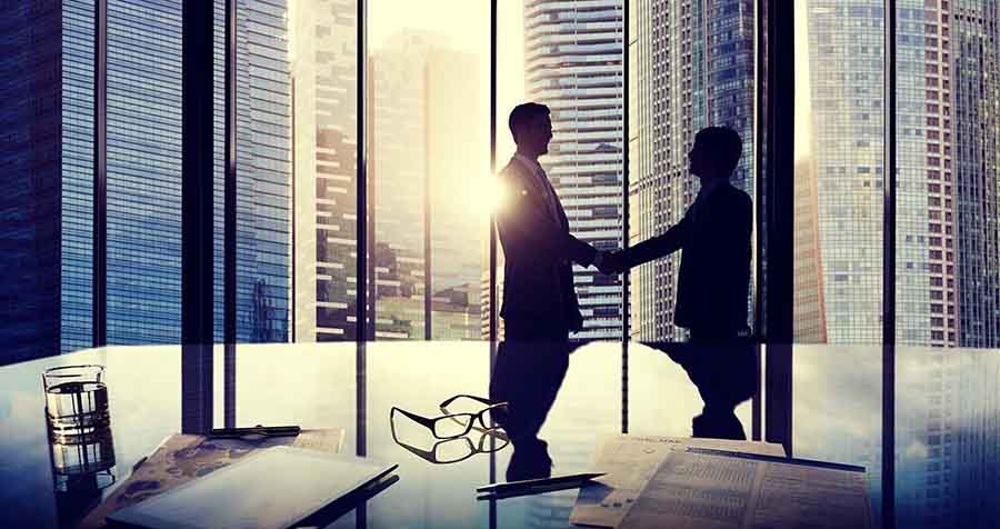 photo of handshake in corporate office
